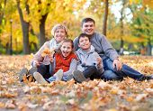 Happy family lies in autumn city park on fallen leaves. Children and parents posing, smiling, playin poster