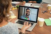 Portrait of smiling man video conferencing on laptop with businesswoman. Woman video conferencing wi poster
