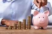 African Man Inserting Coin In Piggybank Near Stack Of Coins poster