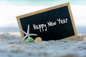 Closeup Of A Chalkboard For Happy New Year Written, Lifebuoy And Starfish On The Sand Of A Beach.  M poster