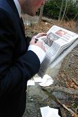 Business Man Reads Paper In The Woods