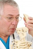 Older doctor surprised to see an empty skull of a skeleton