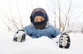Child playing in the snow with snow on his leg