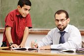 stock photo of student teacher  - Teacher helping pupil in classroom to resolve schoolwork - JPG