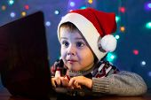 Little Child Writing Letter To Santa Claus On Laptop Computer. Little Boy With Santa Hat. poster