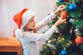 Beautiful Girl Standing At Christmas Tree And Dressing Her With Colorful Toys. She Holds Red One Wit poster