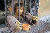 A mannequin in jail begging.