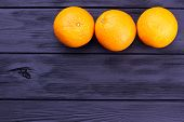 Three Whole Oranges On Dark Wooden Background. Row Of Three Ripe Orange Fruits And Copy Space. Orang poster