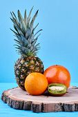 Composition From Exotic Fruits On Tree Stump. Ripe Ananas, Grapefruit, Orange And Kiwi Fruit On Blue poster
