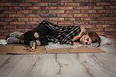 Poor Homeless Woman Sleeping On Floor Near Brick Wall poster
