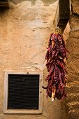 stock photo of chili peppers  - Bunch of chili hanging at adobe wall - JPG