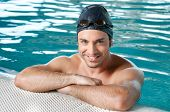 stock photo of breath taking  - Happy smiling swimmer take a break at the edge of a swimmingpool - JPG