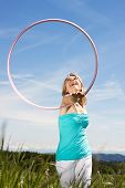 picture of hulahoop  - happy pretty woman standing on a lawn and plays with hula hoops - JPG