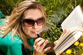 Young Blond Woman With Electric Cigarette Is Reading A Book