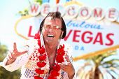 Las Vegas Elvis impersonator laughing having fun in front of Welcome to Fabulous Las Vegas sign.