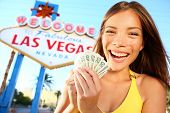 Las Vegas Girl Excited holding money. Winner cheerful by  Welcome to Fabulous Las Vegas sign. Beauti