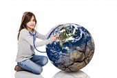 Portrait of a little girl auscultate the health of the planet earth with a stethoscope, isolated on