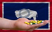 Holding Pills In Hand In Front Of Wyoming Us State Flag