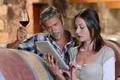 Bodegueros en Bodega utilizando tabletas electrónicas para control de calidad del vino