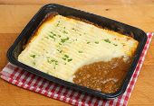 Shepherds pie convenience food in plastic tray with steam rising.