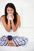 Happy woman drinking coffee in bed at morningtime