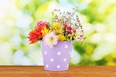 Purple bucket with white polka-dot with flowers on green background