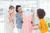 Attractive fashion designers looking at a dress on a mannequin