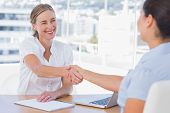 Smiling interviewer shaking hand of an applicant in her office