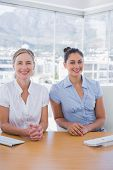 Happy businesswomen sitting side by side at desk in office