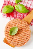 raw burger with basil on a wooden spoon and dishtowel