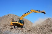 foto of dredge  - Excavator on a pile of rubble against the blue sky - JPG