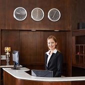 Happy female receptionist behind counter at hotel