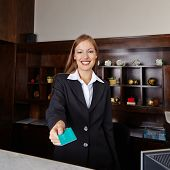 Happy receptionist in hotel offering key card to room