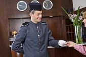Friendly concergie in hotel giving a key card to senior woman