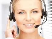 stock photo of receptionist  - picture of friendly female helpline operator with headphones - JPG