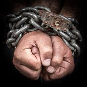 Close-up of two hands chained with an iron chain and a padlock (emerging from a black background)