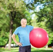 Mature sporty man holding a pilates ball in park