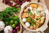Hot and spicy Singaporean Curry Noodle or laksa  mee with hot steam in clay pot, decoration setup, s