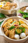 Hot and spicy Malaysian Curry Noodles or laksa  mee with hot steam in clay pot, decoration setup, se