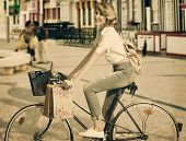 Blonde Girl On Bicycle In Shopping Time
