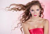Bela jovem, com cabelos longos cacheados em fundo rosa