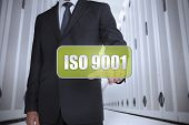Businessman in a data center selecting a green label with iso 9001 written on it