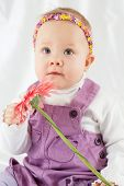 Portrait of little girl in violet pinafore dress with headband in form of chaplet on her head