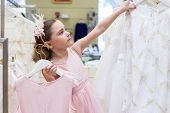 Beautiful girl tries on a dress in a store children clothes
