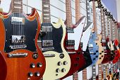 Many electric guitars hanging on wall in the shop