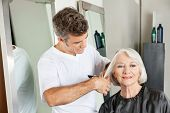 Senior client getting haircut by male hairstylist at salon
