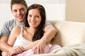 Carefree young couple embracing each other on couch