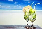 Mojito cocktail with lime and mint on a beach background
