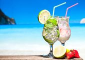 Fruit cocktail and Mojito with blue beach on background