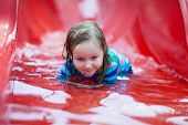 Portrait of little girl on water slide at aquapark